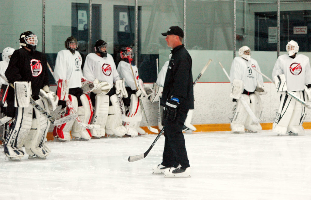 Damian Rhodes teaching a drill to numerous All Pro Goalie Schools students